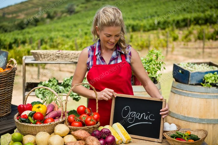 Happy woman holding slate with text at vegetable stall