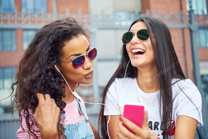 Laughing young friends smiling and taking selfies together outside