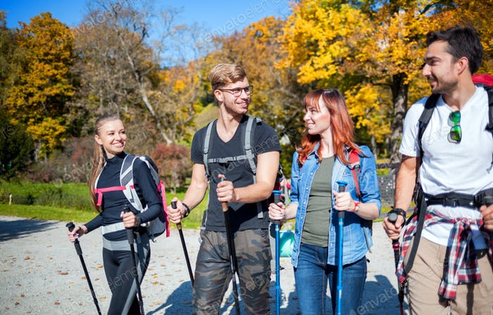 Authentic group of friends on tourist trip walking with backpacks and trekking sticks