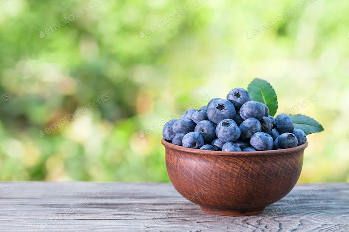 Blueberries in clay bowl on a wooden table