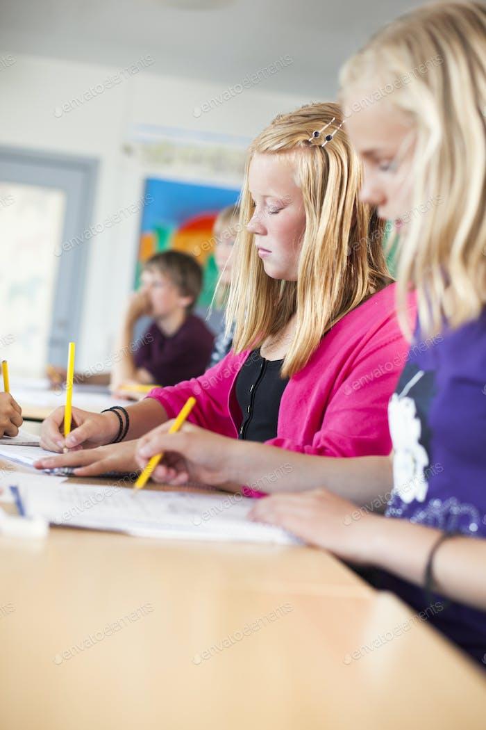 Schulmädchen schreiben am Schreibtisch im Klassenzimmer