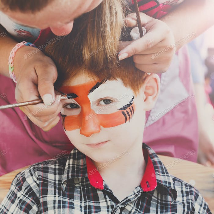 Child boy face painting, making tiger eyes process