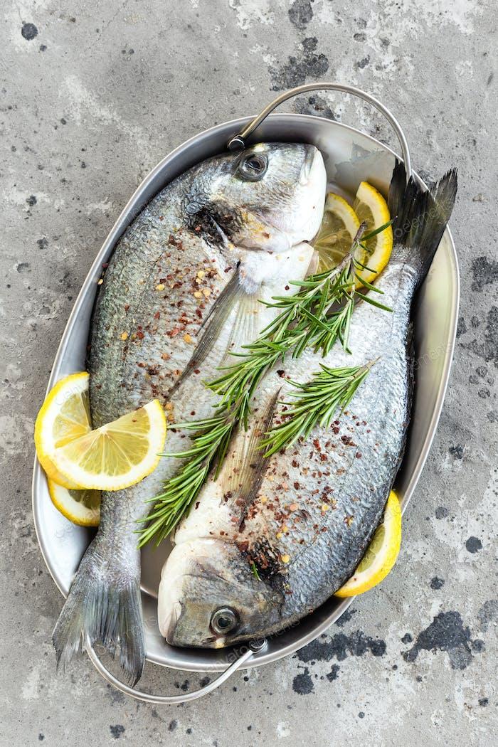 Fresh fish dorado. Raw dorado fish with lemon and rosemary. Sea bream or dorada fish