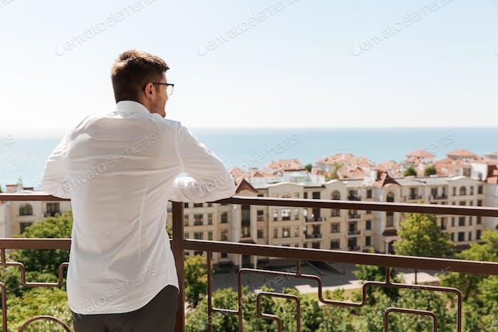 Rückansicht eines jungen Mannes stehend auf einem Balkon