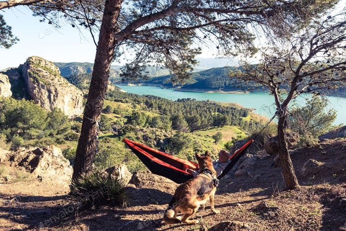 Wanderlust man and dog relaxing at hammock in mountains