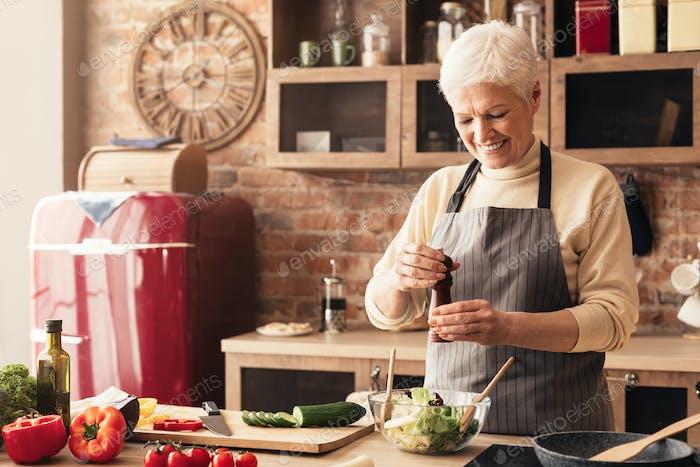 Happy elderly woman seasoning fresh salad with pepper mill