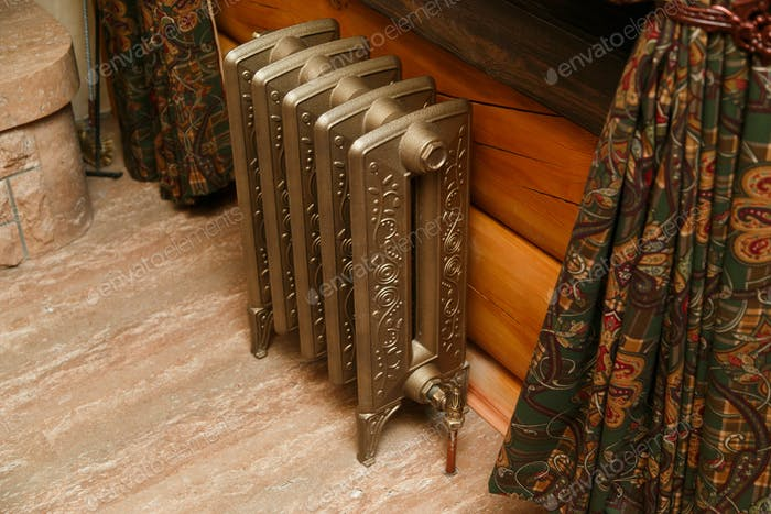 Retro styled cast iron radiator with valve and copper pipe