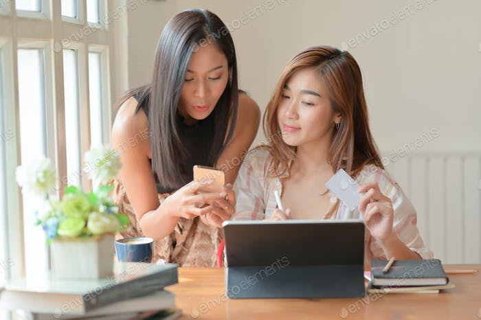 Two Asian women hold a credit card and use a smartphone to search for shopping information.