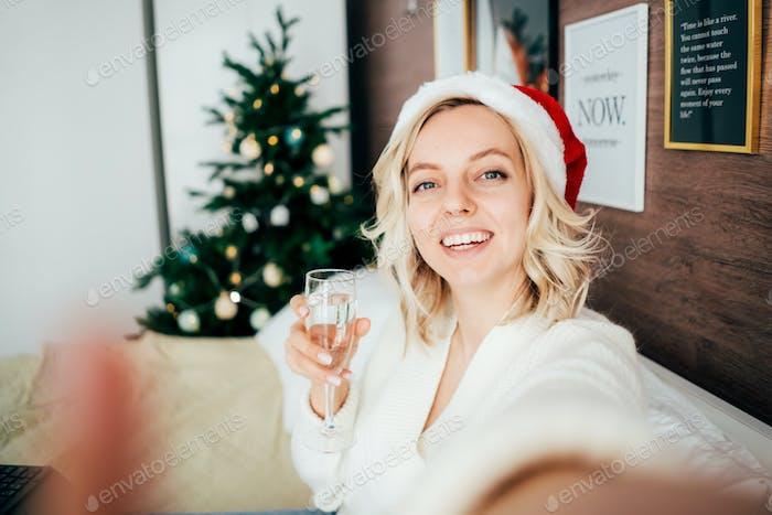 junge Frau macht zu Weihnachten ein Selfie mit einem Glas Champagner. Herzlichen Glückwunsch und Prost