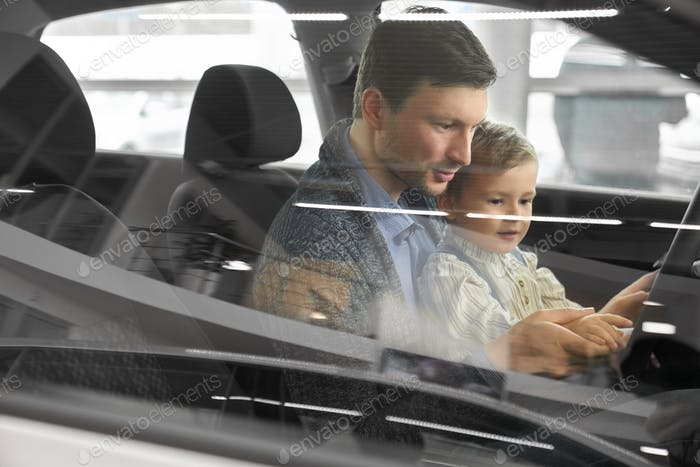 Potential buyer of car testing car with son