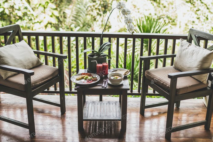 Breakfast outdoor on wooden terrace with jungle view. Eggs, fresh watermelon juice and orchid