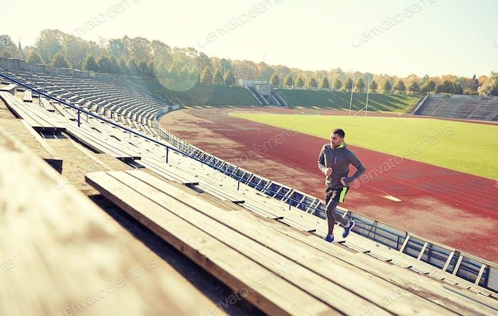 happy young man running upstairs on stadium