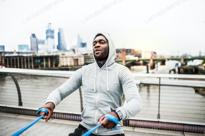 Young black sportsman exercising with elastic rubber bands in London.