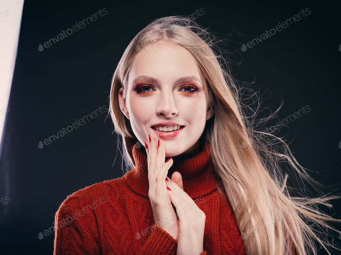 Woman in knitted sweater fashion with blonde long hair autumn stylish over gray background