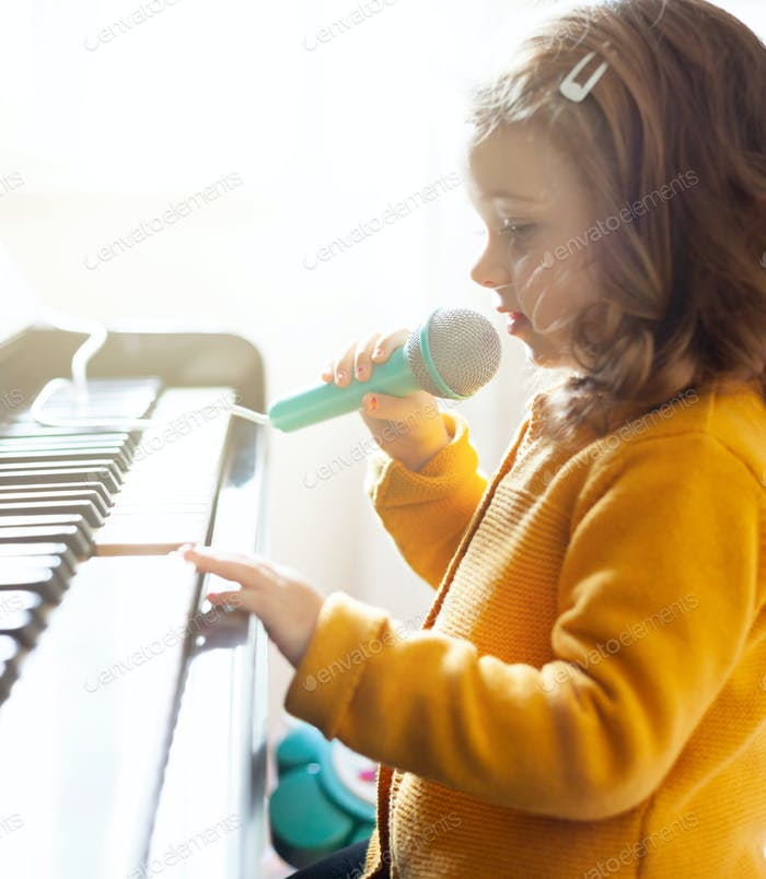Mädchen Kleinkind spielt mit Klavier und Spielzeugmikrofon.