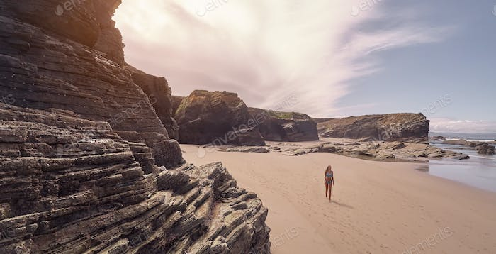 Young woman in bikini taking a walk on a beach full of rocky cliffs in Ribadeo, Galicia