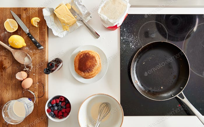 Overhead Shot Of Freshly Made Pancakes Or Crepes For Pancake Day With Maple Syrup And Berries