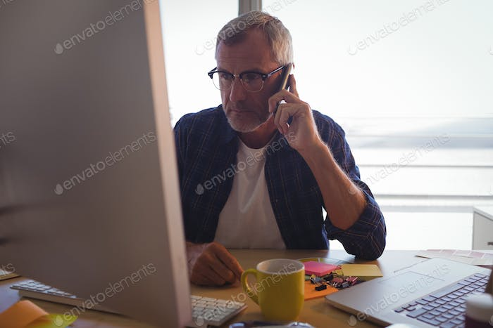 Serious businessman talking on mobile phone at office