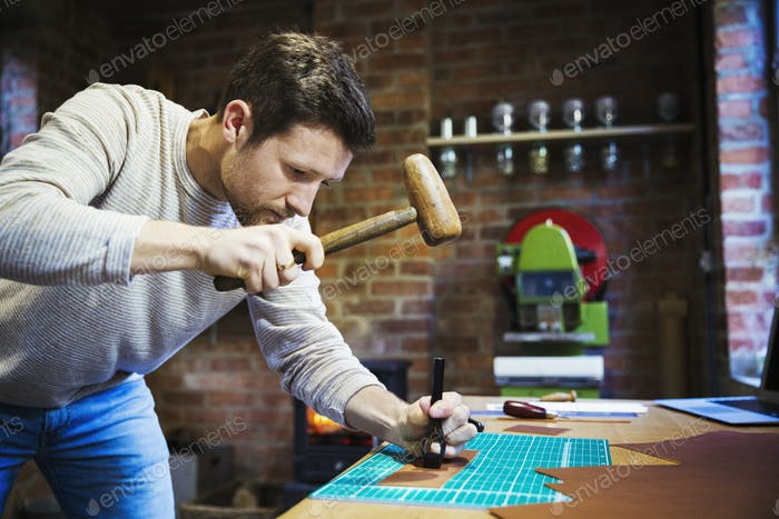A craftsman using a hammer and pincers to hold and imprint a stamp on a piece of brown leather.