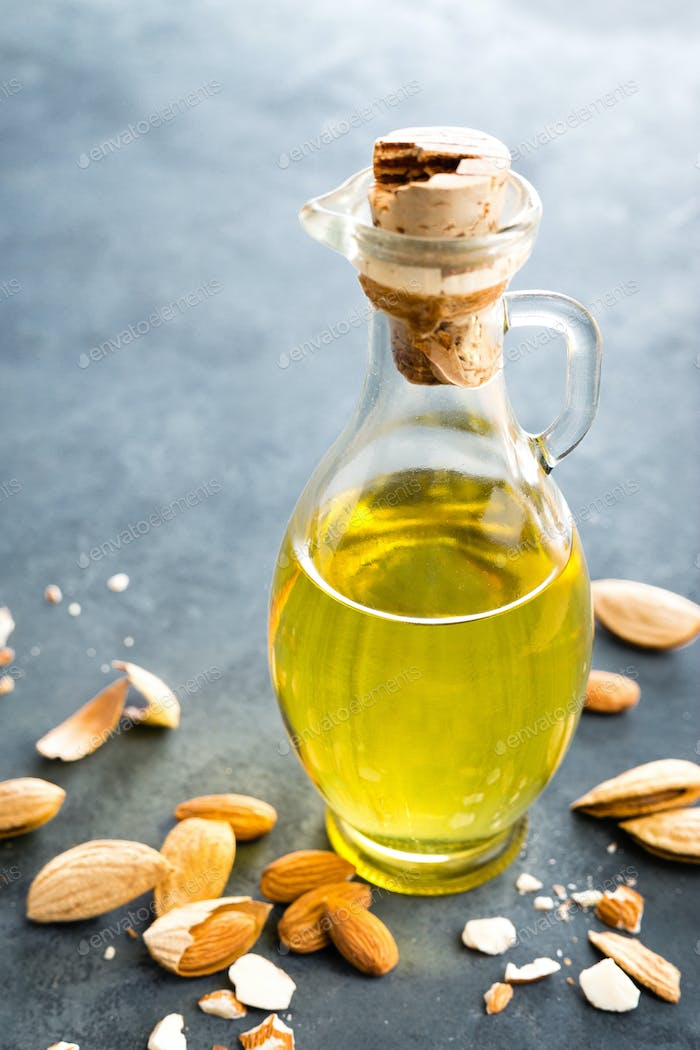 Almond oil in glass bottle and almond nuts. Almonds