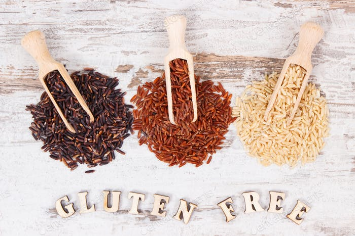 Inscription gluten free with brown, black and red rice on wooden scoops, healthy food concept