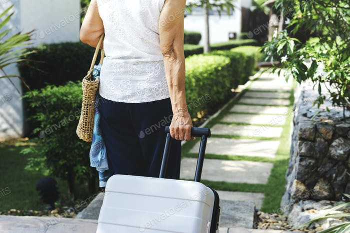 Senior woman pulling suitcase and walking