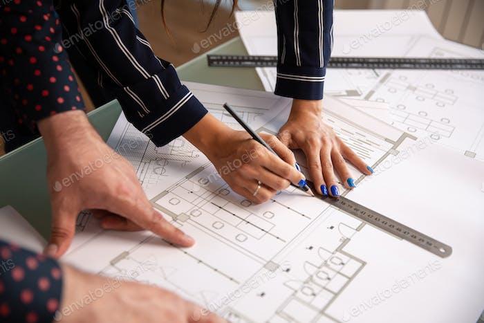 Nahaufnahme mit den Händen von zwei Architekten, die etwas in einem Hausplan zeichnen