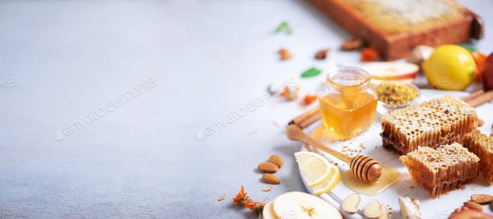 Ingredients for healthy hot drink. Lemon, ginger, mint, honey, apple and spices on grey concrete