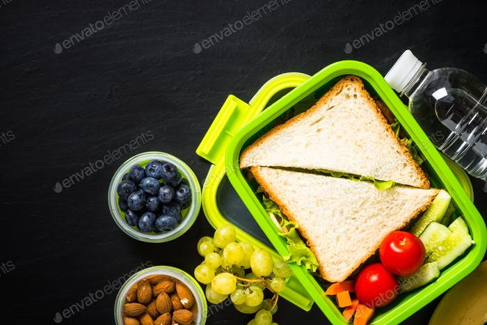 Brotdose mit Sandwich und Früchten auf schwarz
