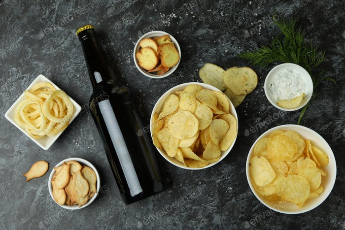Different snacks and bottle of beer on black smokey background