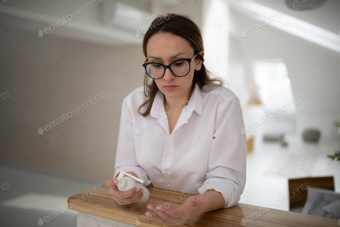 Woman washing hands with sanitizer