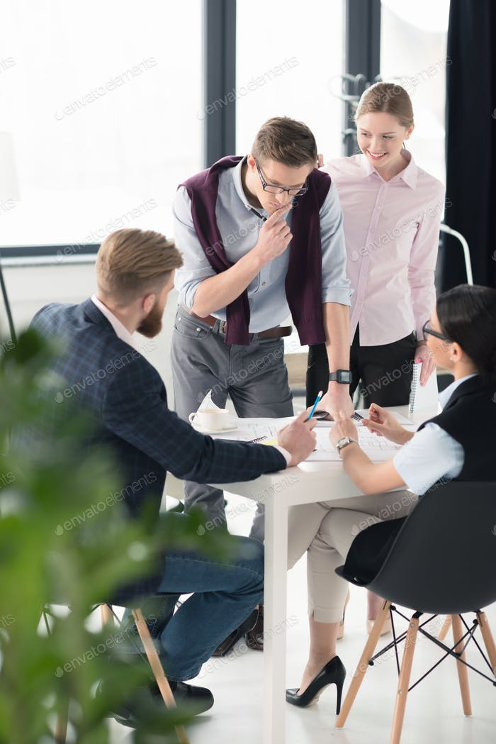Young businessmen and businesswomen discussing business project at workplace