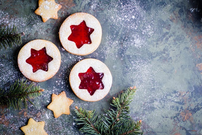 Christmas Linzer cookies with raspberry jam on green table background. Top view and copy space
