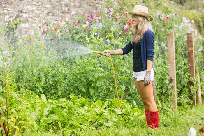 Cute blonde gardening on sunny day at home in the garden