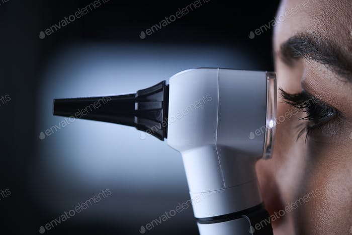 Female doctor using otoscope, side view, close up