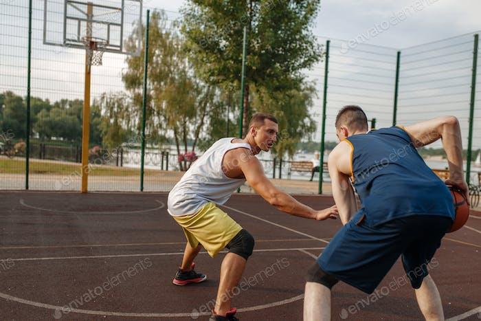 Basketball players playing intense match outdoor