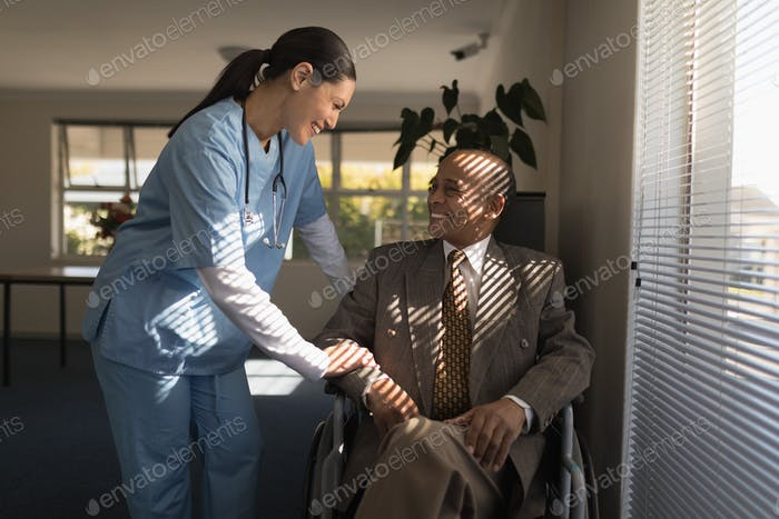 Front view of happy female doctor talking with senior man at nursing home