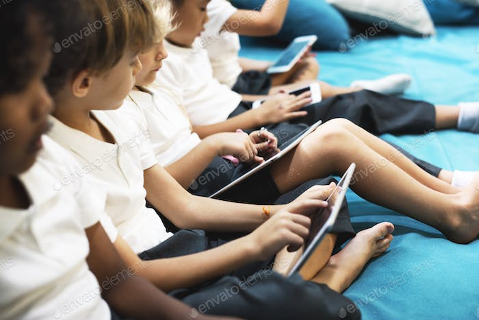 Group of diverse kindergarten students using digital devices