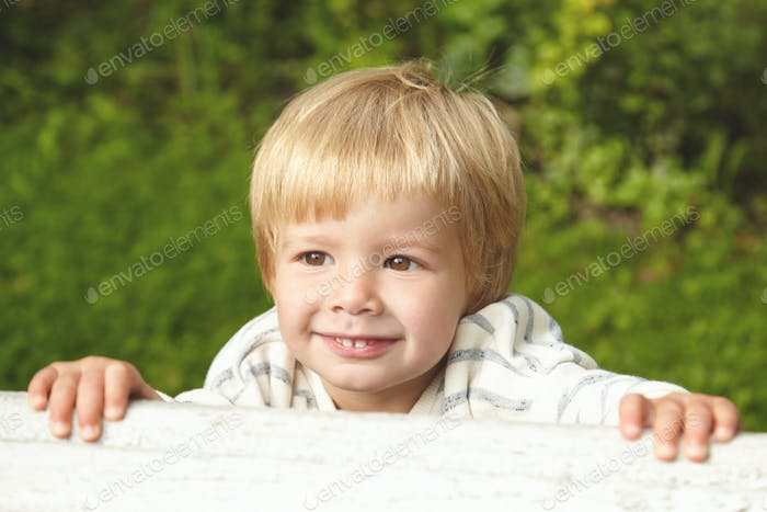 Close-up portrait of Caucasian little five-years old kid. Innocent child smiling with milk teeth and