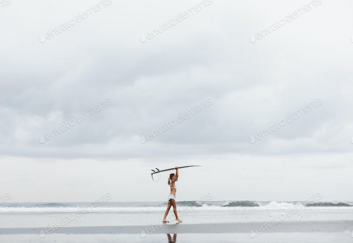 teenage girl in a yellow bikini with her surfboard at a hawaii beach