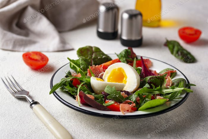 Healthy salad with prosciutto, tomato and egg