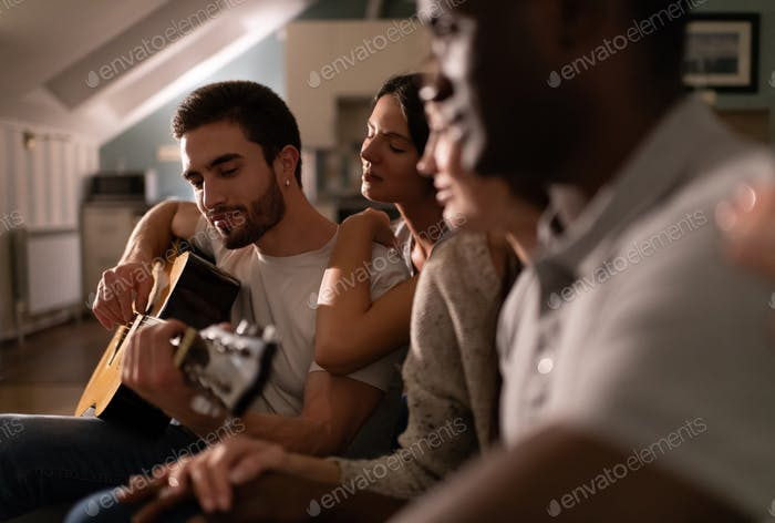 Diverse friends listening to young man playing guitar