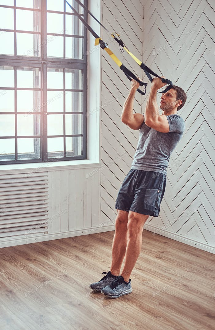 Muscular fitness male doing exercise with TRX. Functional workout at home with TRX loops.