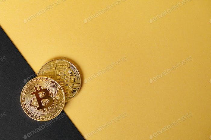 Gold Bitcoin Kryptowährungsmünzen auf geteiltem Gold Gelb und Schwarz Backgound