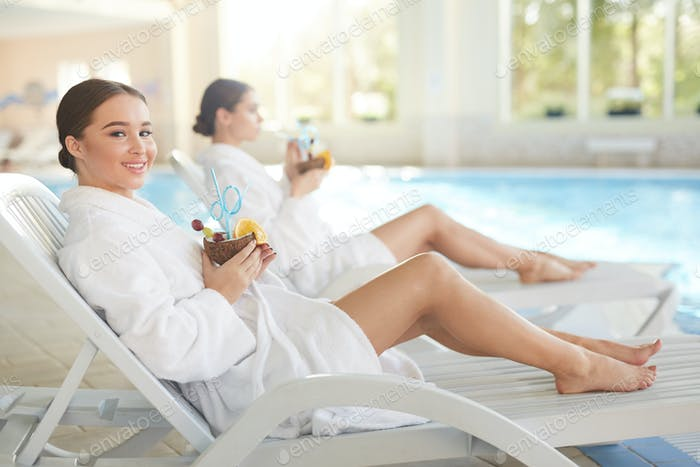 Two Young Women Relaxing by Swimming Pool