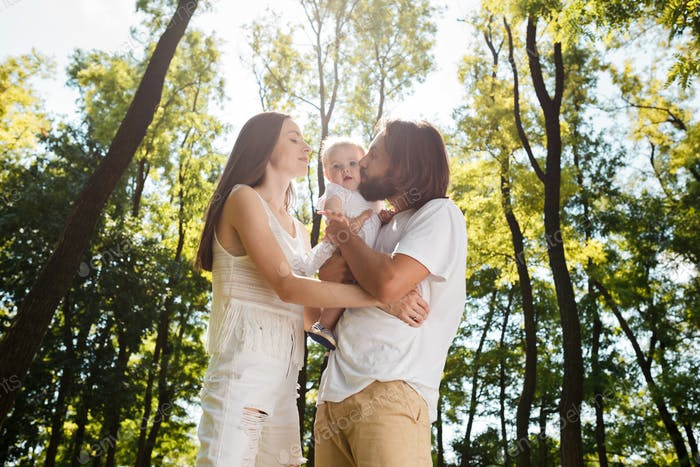 Happy family on the open air. Young dark-haired woman and her husband are kissing their charming