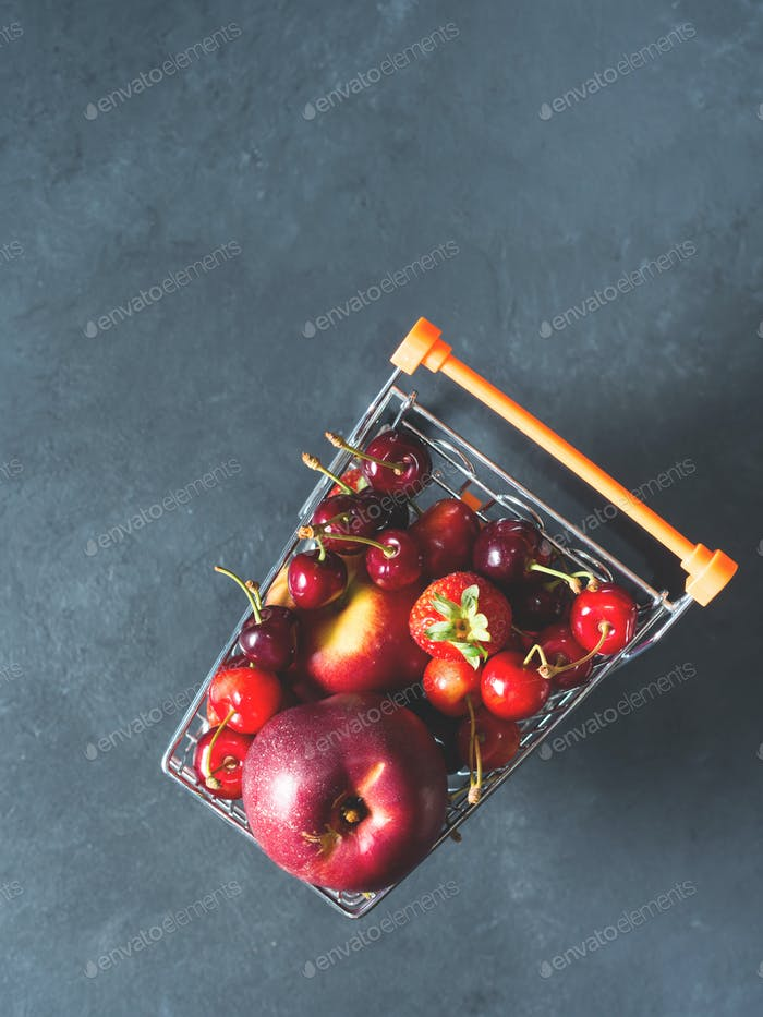 Fresh red fruit berries supermarket cart on black