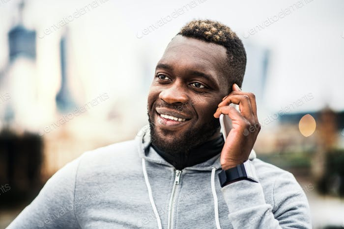 Black man runner with smartphone in a city, making a phone call.