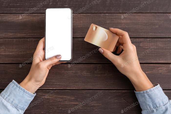 Female hands holding smartphone with blank screen and credit card