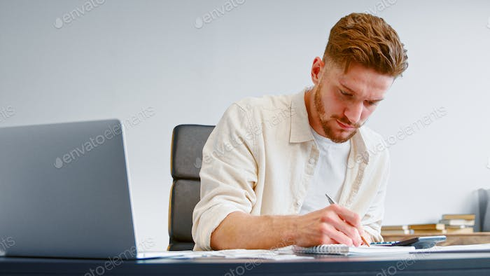 Startup company accountant in yellow shirt summarizes unexpected expenses on calculator